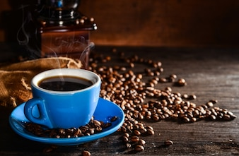 Cup of coffee with coffee beans and grinder background