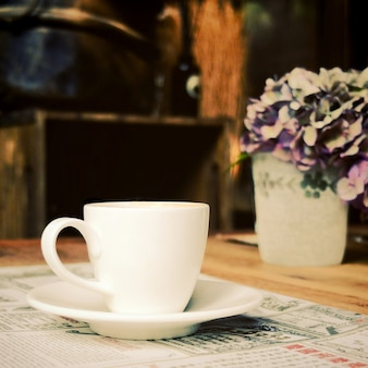 Cup of coffee with newspaper at coffee shop, retro filter effect