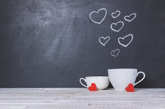 Cup with a blackboard behind with drawn hearts