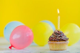 Cupcake with candle and balloons