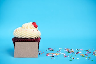 Cupcake with red heart, colorful sprinkles and brown note