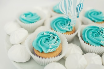 Cupcakes with blue glaze served on white plate