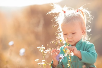 Cute and sweet little girl playing with flowers outdoors