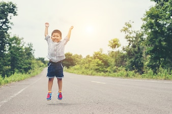 Cute little asian boy jumping on the road.
