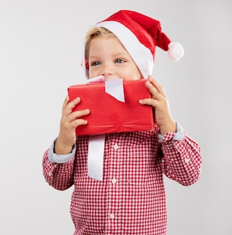 Cute little boy holding a present next to his mouth