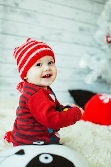 Cute little boy in a red striped hat sits on the floor