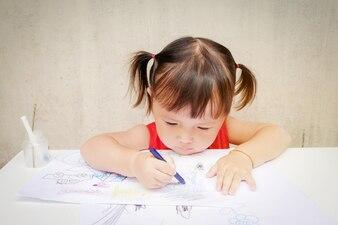 かわいい女の子が幼稚園でクレヨンで描いています