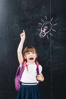 Cute pupil pointing up at blackboard