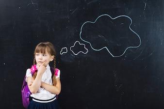 Cute schoolgirl thinking at blackboard