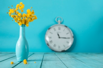 Cute vase with flowers and clock behind