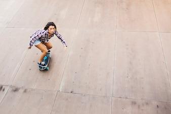 Cute woman skateboarding