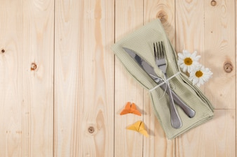 Cutlery and flowers on wooden table