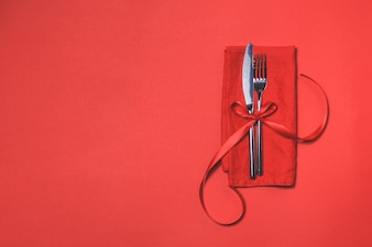 Cutlery tied with a red bow on a red napkin