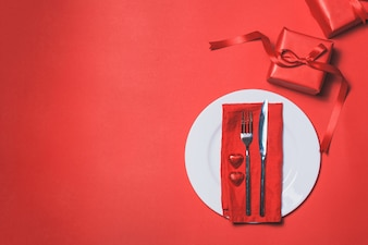 Cutlery with a red gift next to it