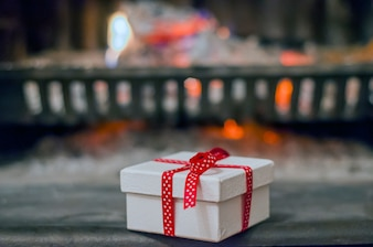 Decorated present with ribbon by the warm cozy fireside. Closeup image of  gift box on wooden table in front of burning fireplace