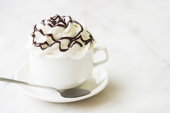 Delicious coffee with whipped cream and chocolate syrup