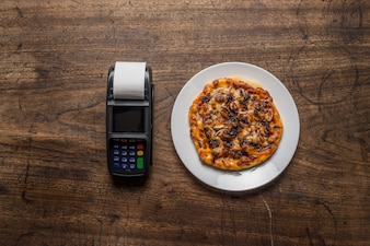 Delicious italian pizzas served on wooden table with payment ter
