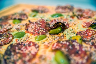 Delicious pizza served on wooden table.  hot tasty delicious rustic homemade american pizza with tomato gherkin salami olives