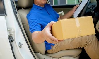 座席に小包を配達する配達ドライバー。