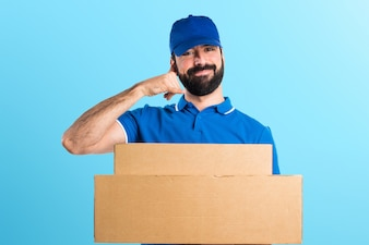Delivery man making phone gesture on colorful background