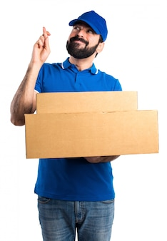 Delivery man with his fingers crossing