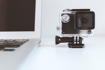 Detail of Action Camera on the white office table and laptop