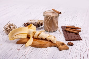 Detox coctail with cinnamon sticks, bananas and chocolate lie on the table