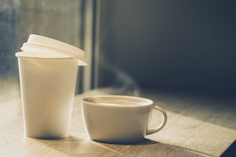 Different cups of coffee - ceramic mug and paper cup to go on wooden table in cafe