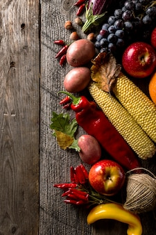 Different seasonal autumn vegetables and fruits on wooden background