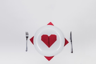 Dish with cutlery and a heart-shaped napkin
