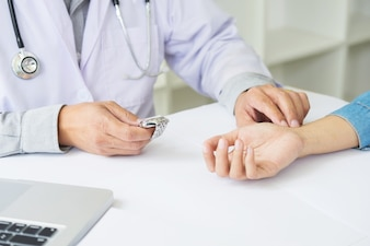 Doctor checking patient heart rate pulse