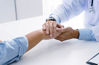 Doctor holding patient's hand, and reassuring his male patient helping hand conceptใ