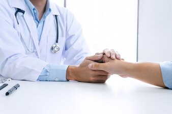 Doctor holding patient's hand, and reassuring his male patient helping hand concept.
