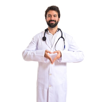 Doctor making a heart with her hands over white background