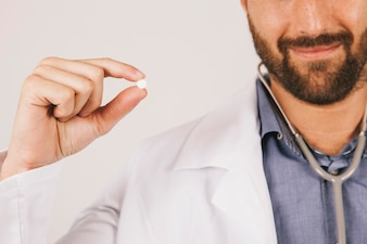 Doctor smiling and holding a pill