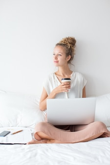 Dreamy Girl Working on Laptop and Drinking on Bed