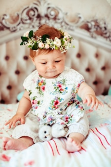 Dreamy little girl in rose wreath sits on soft luxury bed