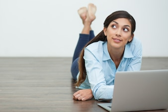 Dreamy Woman Lying on Floor and Working on Laptop