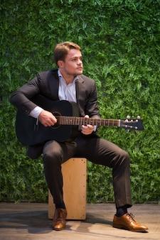 Dreamy young man enjoying playing guitar in cafe