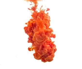Drop of orange paint falling in water