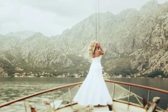 Dynamic stylish blonde bride posing on the deck of a yacht on the background of sea and mountains Montenegro