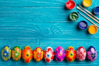 Easter eggs in row with paint brushes and paint jars