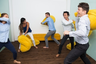 Ecstatic multiethnic friends fighting pillows