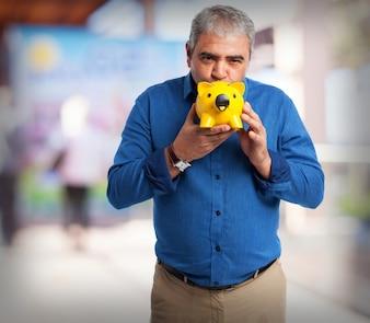 Elderly man kissing a piggy bank yellow