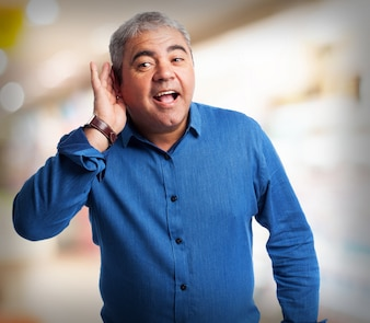 Elderly man pretending not to hear with one hand on his ear