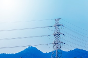 Electricity transmission pylon silhouetted against blue sky at d