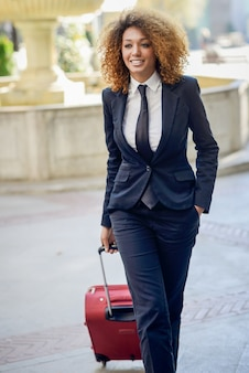 Elegant businesswoman with her red suitcase