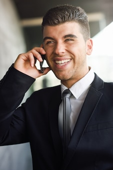 Elegant executive laughing while talking on phone