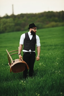 Elegant man posing with a chair in the field