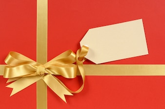 Elegant red gift with a golden bow and tag